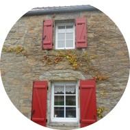volets battants en aluminium à barres et écharpes - rouge brun - sur maison en pierre